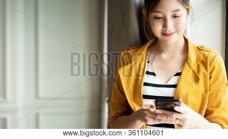 Asian Woman Standing Side Window With Beautiful Smile And Using Application Chatting On Cell Smartph
