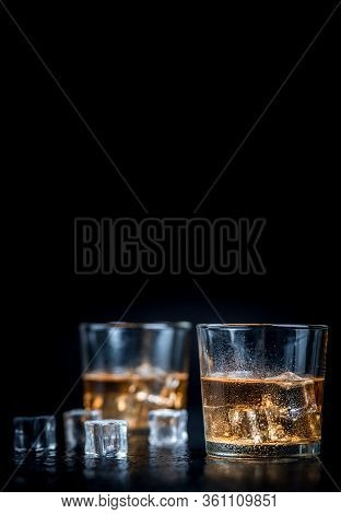Whisky, Whiskey, Bourbon Or Cognac With Ice Cudes On Black Stone Table