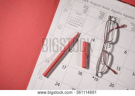 Closeup Of A Red Pen And Glasses On A Open Calendar. Calendar Open On A August Page On A Red Backgro