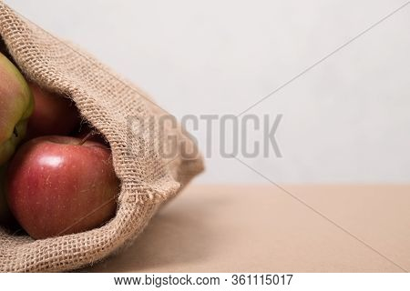 Bag With Apples. Studio Image. Red Apples In A Burlap Bag On A Wooden Background. Fabric Bag Full Of