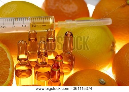 Vitamin C. Glass Ampoules Set , Syringe Among The Fruits Of Oranges And Lemons On A White Background