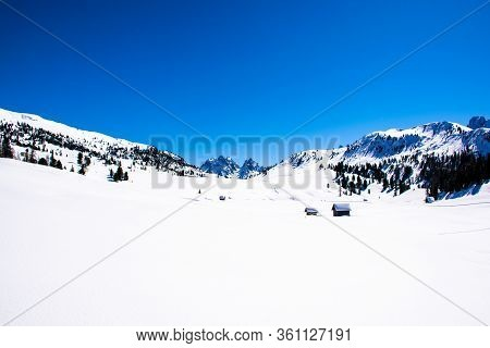 Expanse Of Snow On The Plateau Of Prato Piazza With The Typical Wooden Houses On The Background A Bl