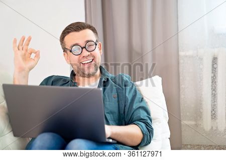 Man Freak With Glasses, Blogger, Freelancer, Businessman Working Online Lying On The Couch. Social D