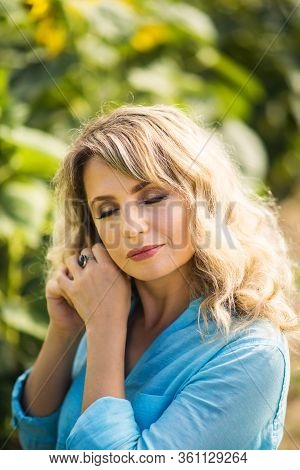 Vertical Close-up Portrait Of Beautiful Blonde 40 Years Old Woman With Closed Eyes In Blue Shirt Tou
