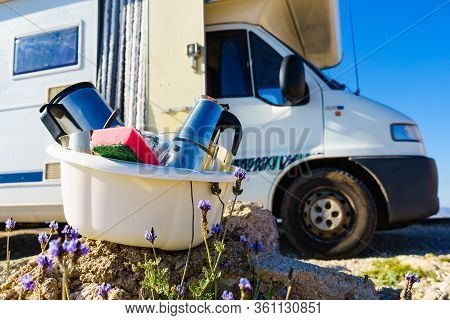 Bowl Full Of Dirty Dishes Outdoor Against Camper Vehicle. Washing Up On Fresh Air. Adventure, Campin