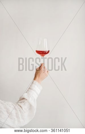 Womans Hand Holding Glass Of Rose Wine Over White Wall