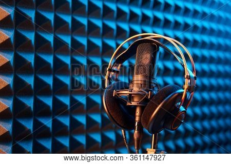 Studio Condenser Microphone With Professional Headphones On Blue Acoustic Panel