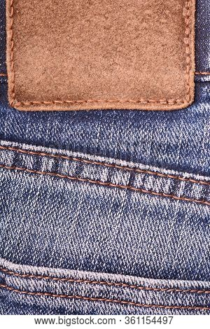Leather Label On Denim Jeans Background, Close Up. Brown Leather Tag, Double Seams, Strap On Dark Bl