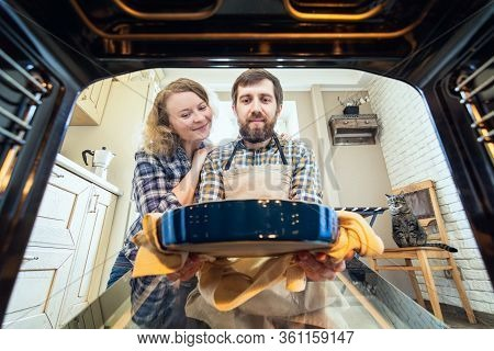 Smiling Eastern European Couple Cooking At Home. Man Taking Out A Pie From The Oven With Kitchen Int
