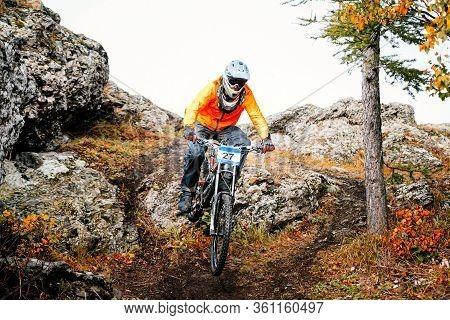 Man Rider In Orange Jacket Downhill Mountain Biking