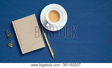 Top View Office Coffee Break Concept. Flat Lay Cup Of Coffee, Paper Notepad And Golden Office Supply
