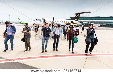 Johannesburg, South Africa - November 27, 2014: Passengers Disembarking A Small Charter Propeller En