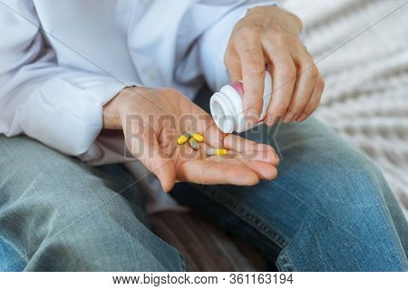 Female Hand Close Up Holding A Medicine, Elderly Woman Hands With Pill On Spilling Pills Out Of Bott