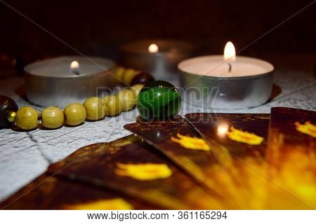 Mystical Still Life. Burning Candles And A Magic Glass Ball And Cards On A Dark Background. The Conc