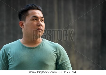 Face Of Young Overweight Asian Man Thinking Outdoors