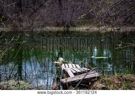 A Wooden Platform On A Quiet Lake With Clear Water And Reflected Trees. Symbol Of Calm And Solitude
