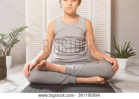 Lotus Position. Meditation. Pranayama. Children Yoga At Home. Boy Wearing Gray Clothes Sitting On A