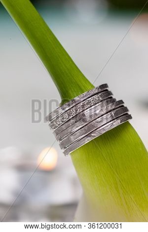 Close-up Of Two Wedding Rings And The Wedding Bouquet Of Beautiful White Zantedeschia Aethiopica Or