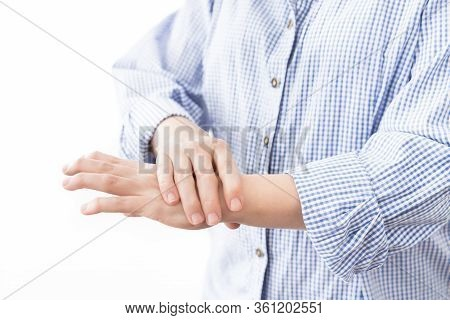 Young Woman In Casual Blue Shirt Suffering From Pain In Hands. Health Care Concept With Real Rheumat