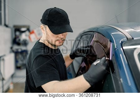 Closeup Image Of A Handsome Car Mechanic Worker, Wearing Black Uniform, Attaching Tinting Foil To Ca