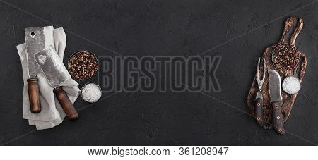 Vintage Chopping Board With Meat Hatchets And Fork With Knife On Black Background With Salt And Pepp