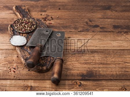 Vintage Hatchets For Meat On Wooden Chopping Board With Salt And Pepper On Wooden Background.