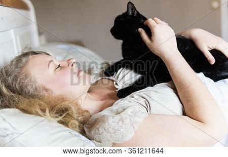Young And Smiling Eastern European Woman Lying In Bed With Black Cat In Her Hands In The Morning.