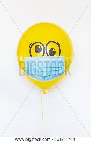 Yellow Balloon With A Medical Mask And Doodle Shocked Eyes. Conceptual Image Of Birthday Party Durin