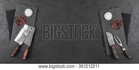 Stone Chopping Board With Meat Hatchets And Fork With Knife On Black Background With Salt And Pepper