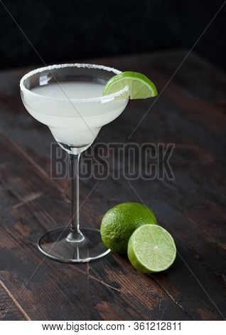 Classic Glass Of Margarita Cocktail With Fresh Limes On Wooden Table Background.