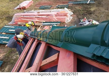 The Worker Installs And Attaches A Metal Tile To The Roof Of The House.