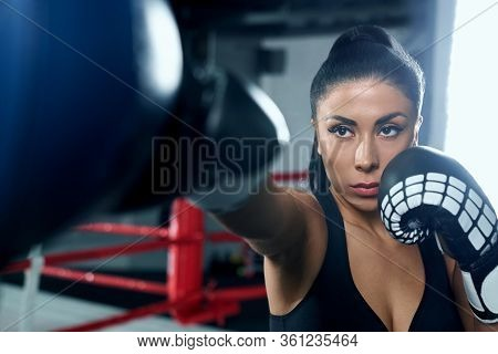 Front View Of Muscular Woman With Strong Face Wearing Boxing Gloves And Hitting Boxing Bag. Young At