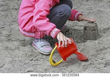 Children's Games In The Sandbox On The Playground.