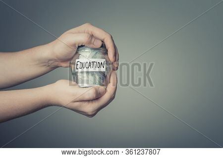 Education Savings Concept. Man Hands With Glass Jar Full Of Us Dollars.