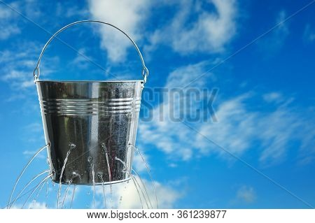 Leaky Bucket With Water Against Blue Sky. Space For Text