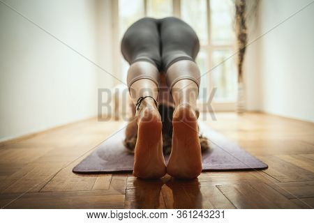 Close Up Of A Young Woman Is Doing Stretching Exercise On Floor Mat In Morning Sunshine. She Is Medi