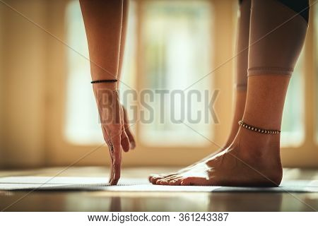 Close Up Of A Young Woman Is Doing Yoga Meditation In The Living Room At Home. She Is Stretching On