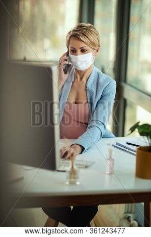 Business Woman In A Medical Protective Mask Using Smartphone And Works At The Office On The Computer
