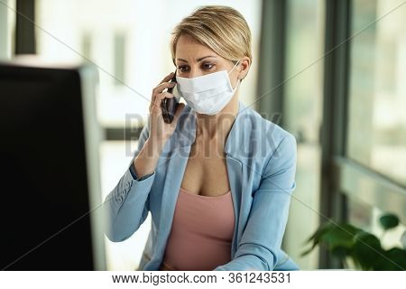 Business Woman In A Medical Protective Mask Works At The Computer And Talking On A Smartphone During