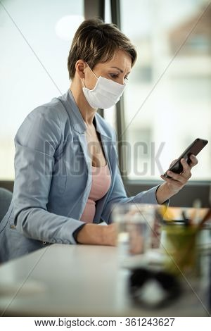 Business Woman In A Medical Protective Mask Surfing At Social Network At The Smartphone And Works Fr