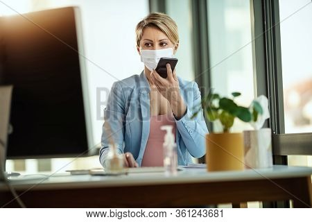 Business Woman In A Medical Protective Mask Talking On A Smartphone And Works At The Office On The C