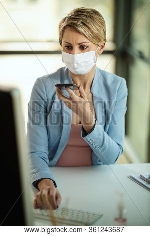 Business Woman In A Medical Protective Mask Talking On A Smsrtphone And Works From Home At The Compu