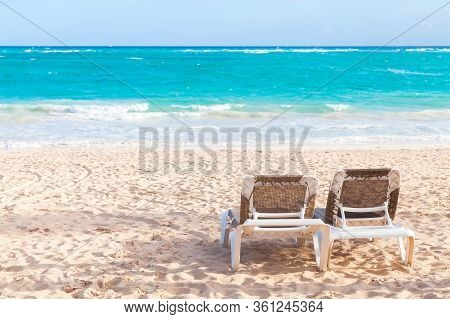 Two Vacant Sunloungers Are On Sandy Beach At Sunny Day