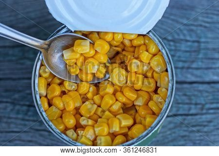 Open Tin Can With Yellow Tinned Corn And A Small Metal Spoon On A Gray Table