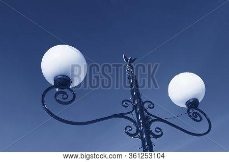 Lantern Against A Clear Blue Sky. Hoarfrost On The Lantern. Little Bird Decorates A Lantern. Photo T