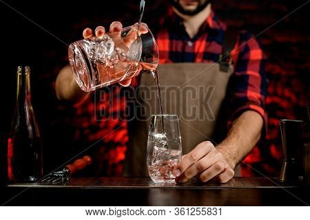 Professional Bartender Accurate Pours Cocktail From Mixing Cup Into Small Glass.