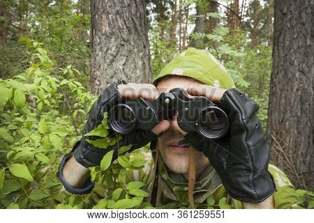 Spotter In Camouflage Overalls Is Monitoring Enemy From From Forest Thickets