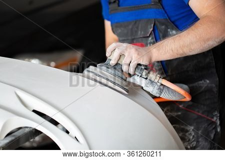 A Man Who Sanding With A Grinder And Prepares The Paint For The Car In A Car Service. Repairman Fix
