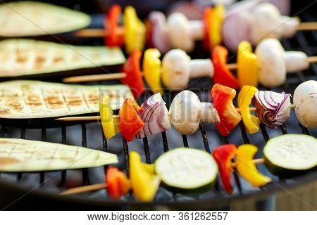 cooking, barbecue and food concept - close up of eggplant slices and vegetables with champignon mushrooms on bamboo skewers roasting on hot brazier grill outdoors