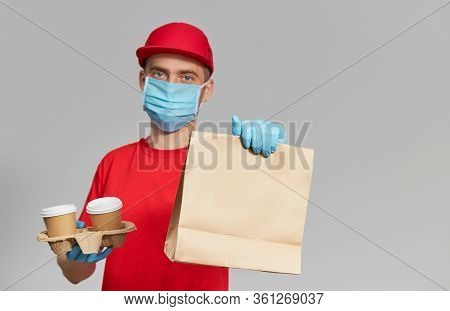 Courier In Protective Mask And Medical Gloves Delivers Takeaway Food And Coffee. Delivery Service Un